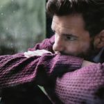 a photo of a man in a sweater looking concerned, and looking outside at the rain