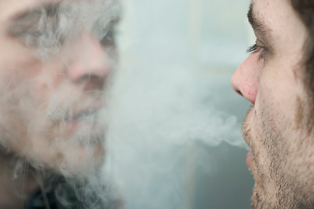a photo of two people, cigarette smoke in between them