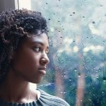 a Black woman looking out the window as it rains